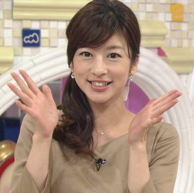 ベージュのトップスで両手を開き微笑むアナウンサー、生野陽子